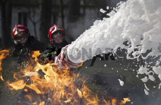 Firefighters extinguish a fire. Lifeguards with fire hoses in smoke and fire.