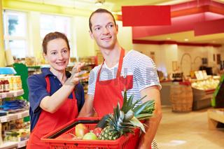 Kauffrau hilft Azubi im Supermarkt