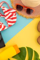 Flip flops, sunhat, bikini and camera on yellow and blue