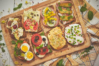 Tasty, homemade small sandwiches with various ingredients served on wooden chopping board