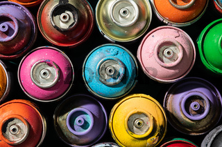 Top view of used spray paint cans with multiple colors