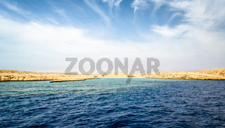 rocky coast of the Red Sea andblue sky with clouds
