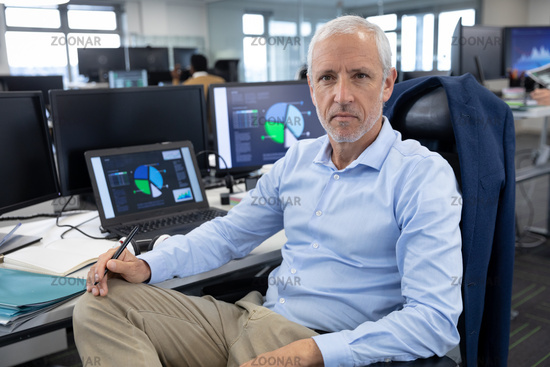 Portrait of senior businessman sitting on his desk at modern office