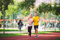 Couple of kids boy and girl doing cardio workout, jogging in park on jogging track red. Cute twins runing together. Run children, young athletes. Teen brother and sister running along path outdoors
