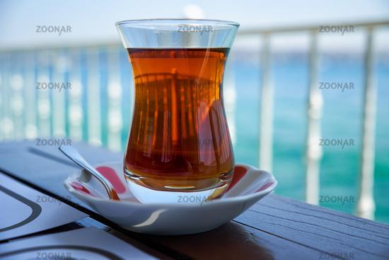 Tradition Turkish bardak with black tea on the background of Bosphorus strait . Istanbul. Turkey.