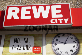 Rewe City logo sign and opening times of german supermarket chain