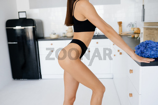 Beautiful young girl posing in lingerie in the kitchen