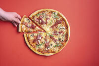 Woman grabbing a slice of pizza. Pizza ham top view