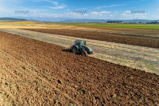 aerial view of the tractor plows in the field,