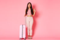 Travelling, holidays and vacation concept. Full-length of indecisive attractive asian girl making choice, pointing finger up while looking serious camera, standing with suitcase, pink wall