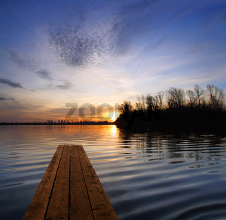 river landscape with pier and sunset on river