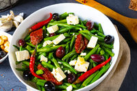 Spicy green bean salad with olives, feta cheese and dried tomatoes