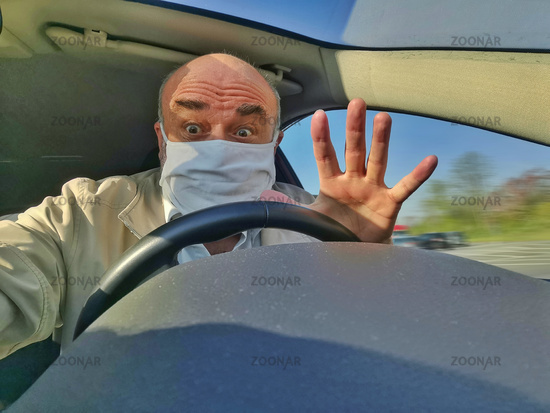 Senior with face mask and hand raised behind the wheel of a car.