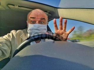 Senior mit Maske im Auto