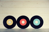 Vinyl records on yellow wooden background