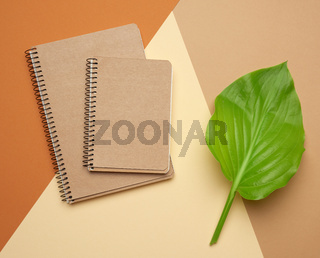 stack of spiral open notebooks with blank brown sheets on a beige background