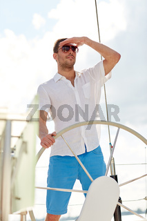 young man in sunglasses steering wheel on yacht