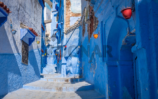 Alleway with colorful pots in Chefchauen, the Blue City of Morocco