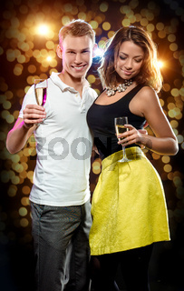 Young attractive couple with glasses of sparkling champagne over abstract golden background