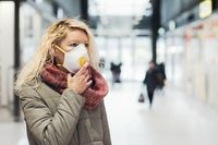 COVID-19 Pandemic Coronavirus Young girl in city street wearing face mask protective for spreading of Coronavirus Disease 2019. Close up of young woman with surgical mask on face against