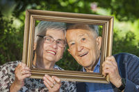 Retired couple hold a frame and looking through