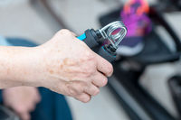 A female senior citizen uses a hand muscle trainer at home