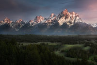 A view overlooking the Grand Tetons mountains with fog rolling through