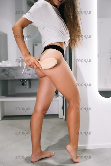 Sexy brunette girl in black underwear with a hair brush