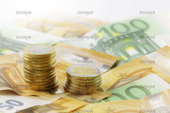 Euro coins in pile on Euro banknotes, panorama, background.