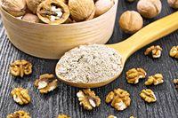 Flour walnut in spoon on dark wooden board