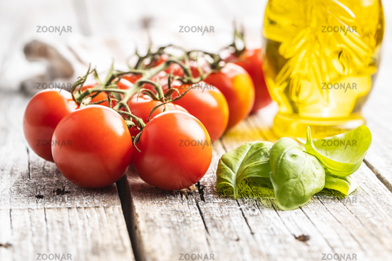 Red cherry tomatoes and basil leaves on wooden table.