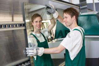 Glazier putting glass in grinding machine