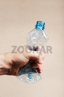 Male hand holding squashed plastic bottle