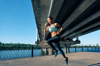 Sporty woman running outdoors by river