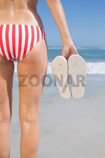 Mid section of fit woman in bikini on the beach holding flip flops