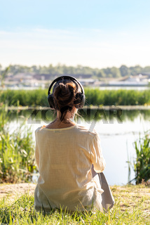 Woman with headphones is meditating, sitting in front of the river,  just after the sunrise.