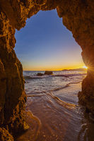 View from the beach through a rock formation to the Atlantic ocean, sunset at Algarve coast