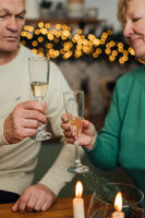 Happy elderly couple celebrating wedding anniversary. 60s happy retirement. Valentines seniors day. Champagne date