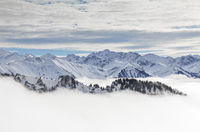 Snow covered mountains with inversion valley fog and trees shrouded in mist. Scenic snowy winter landscape in Alps, Allgau, Kleinwalsertal, Bavaria, Germany.