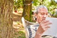 Senior Mann im Ruhestand beim Buch lesen