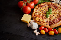 Fresh baked, hot american style pizza with all various ingredients on side