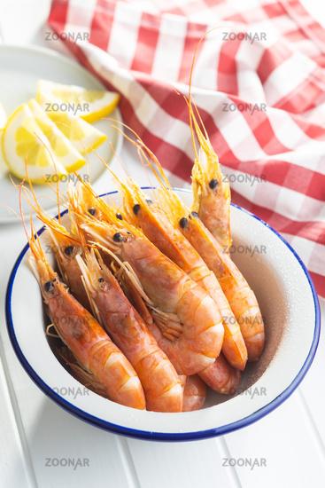 Boiled tiger prawns in bowl on white table. Tasty shrimps.