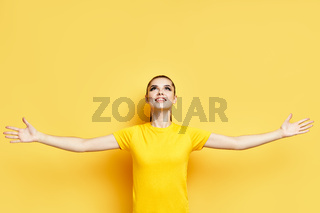Happy freedom young woman with raised hands looking up on copy space
