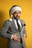 Overeating, improper nutrition during the New Year holidays handsome bearded man in Santa blue hat and grey suit, looking at camera isolated on yellow background