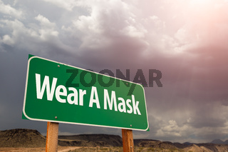 Wear A Mask Green Road Sign Against Ominous Stormy Cloudy Sky