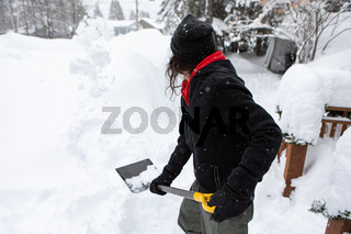 Man holding shovel while shoveling snow.