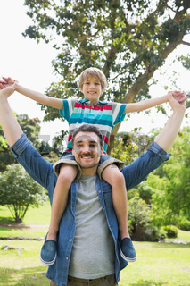 Father carrying boy on shoulders in park