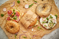 Bagels with ham, cream cheese, hummus, radish wrapped in brown baking paper ready for take away