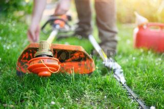 Gardener preparing grass trimmer on lawn in garden outdoors.