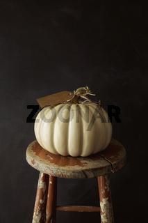 White pumpkin on old stool